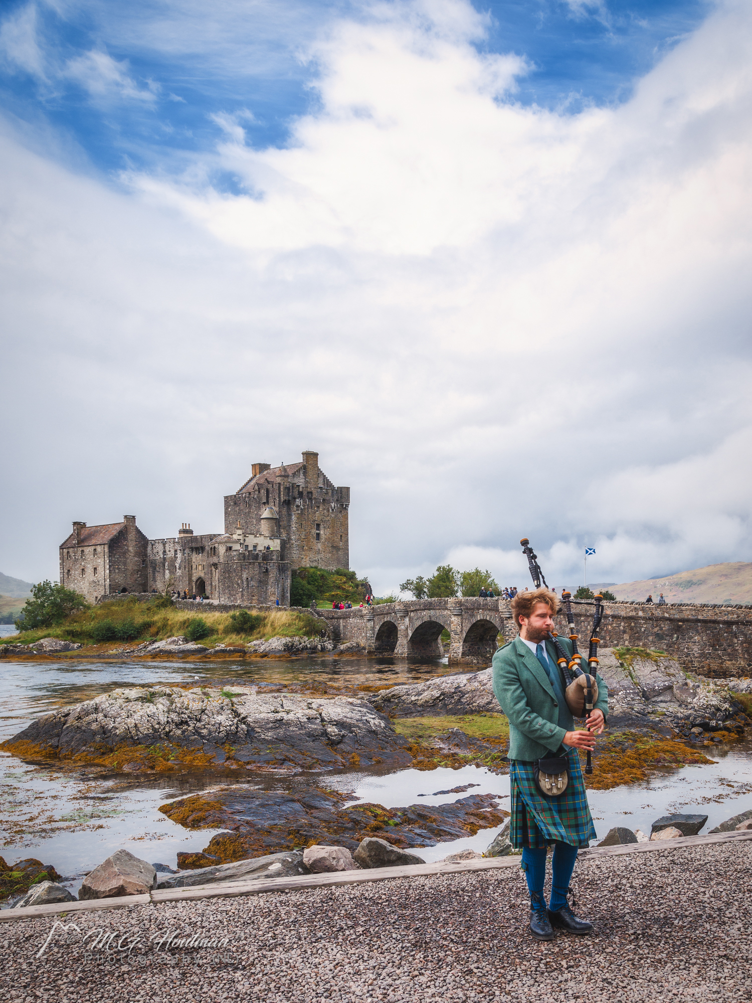 Bagpipe player in front of Eilean Donan Castle
