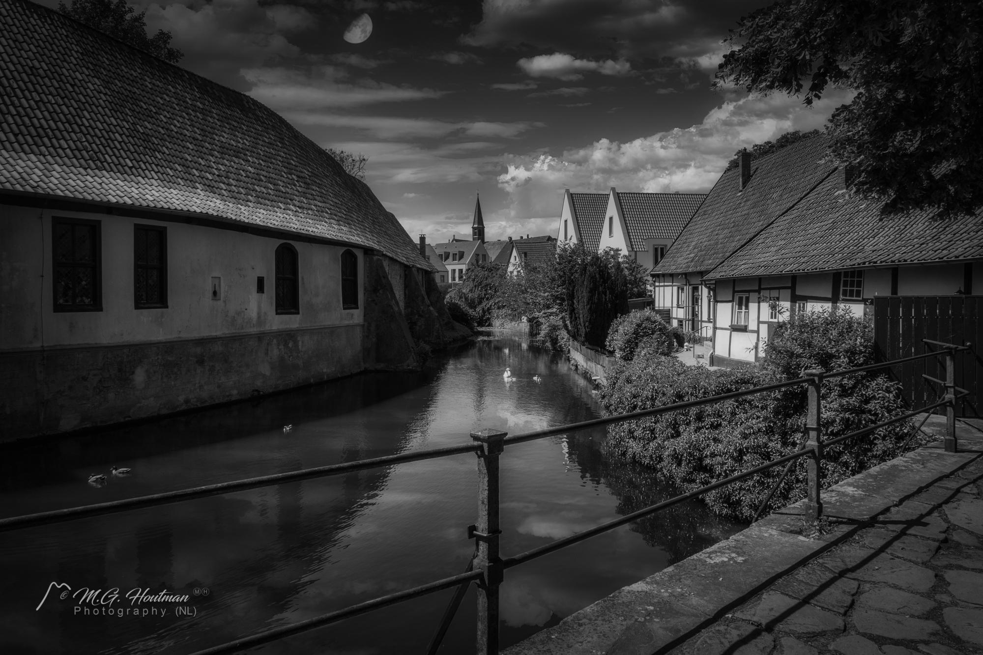 """Es verleiht dem Eingang zur Innenstadt Burgsteinfurt etwas Pompöses, etwas Adliges und einen ganz besonderen Charme. Ja, es lässt eine Kulisse entstehen, die vor allem in den Sommermonaten nicht schöner sein könnte.  Das Schloss, eine der ältesten, mächtigsten und schönsten Wasserburgen des Münsterlands, wurde im Laufe der Zeit mehrmals zerstört und wieder aufgebaut und erweitert und zeigt heute noch facettenreiche Elemente aus Romanik, Rokoko und Klassizismus. Weil die Landschaft weder hohe Berge noch schroffe Klippen ausweisen konnte, ließen die damaligen Baumeister breite Wassergräben und künstliche Inseln anlegen, auf denen sie ihre Festungsanlage errichteten.  Ebenfalls erschufen die """"Edlen Herren"""" das Fundament für die Stadt Steinfurt: Im Schutze der Burg entstand die erste Marktsiedlung, die """"Statt o Stenvorde"""".  Heute bewohnen die Nachfahren der Erbauer, die Familien des Fürsten zu Bentheim und Steinfurt, das Schloss. Aus diesem Grunde ist eine Besichtigung derzeit auch nicht möglich – die Fürstenfamilie bittet hier um Verständnis."""